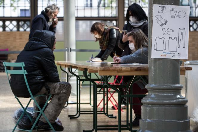 Un membre de l'association Aurore accueille une personne sans abri pour une distribution de nourriture et de vêtements, le 31 mars, à Paris.