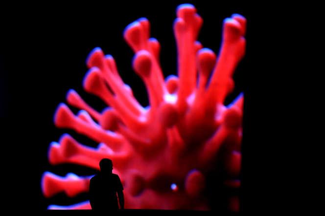 Un homme passe devant un écran géant pendant l'épidémie de Coronavirus, à Brasilia (Brésil), le 24mars.