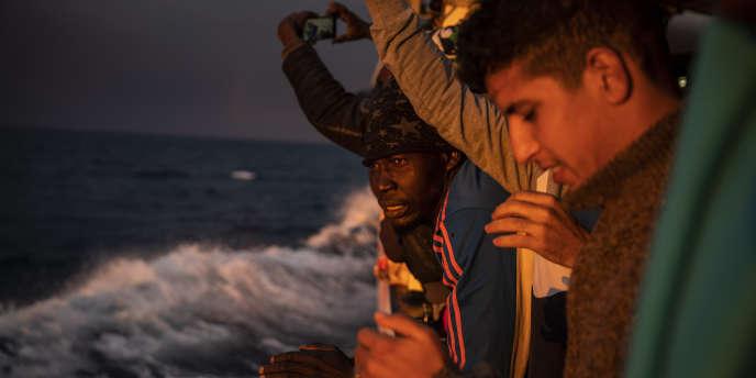 Le 12 janvier 2020, des hommes originaires du Nigeria et du Maroc regardent le coucher du soleil depuis le bateau Open Arms venus en aide à de nombreux naufragés au large des côtes libyennes (AP Photo/Santi Palacios, File).