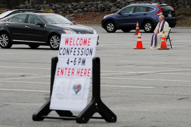 Le père Brian Mahoney participe à un drive-in pour les confessions sur le parking de l'église Sainte-Mary à Chelmsford, dans le Massachusetts, mercredi 1er avril.