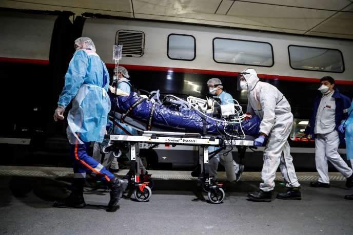 Du personnel médical embarque un patient atteint du Covid-19 à la gare d'Austerlitz, àParis, le 1eravril.