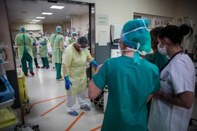 Les soignants en blanc viennent du service de réanimation, ceux en vert sont les infirmiers anesthésistes et les aides-soignants du bloc opératoire. La présence des équipes de réanimation rassure leurs collègues du bloc. Pour beaucoup, la réanimation est une nouveauté. Par contre, tous ces soignants sont familiers avec le respirateur artificiel et les patients intubés, qui font partie du quotidien habituel au bloc opératoire.