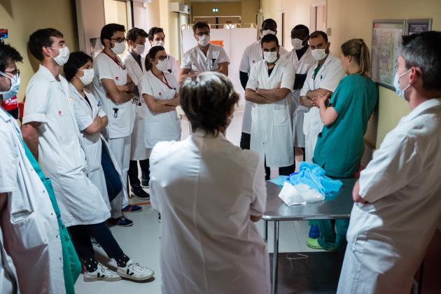 Bénédicte, anesthétiste (en vert) forme des internes sur la manière de revêtirla tenue de protection. Ces jeunes internes vont prêter main forte aux équipes de réanimation, notamment pour les manœuvres de retournement des patients.