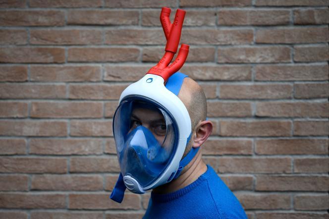 Le designer Mario Milanesio pose avec un masque Decathlon avec des raccords de valves respiratoires imprimées en 3D, le 26 mars àSavillan (Italie).
