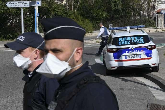 Des policiers contrôlent des automobilistes avec le message « Restez chez vous» sur leur voiture, le 1er avril à Marseille.