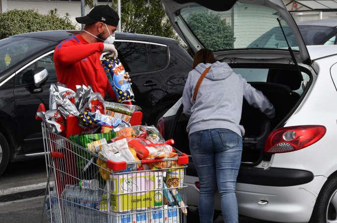Sur le parking d'un supermarché, à Montpellier, des consommateurs rangent leurs courses, lundi 30 mars.