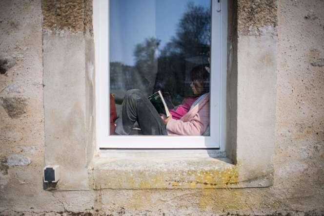 Une jeune fille lit à la maison, en période de confinement, le28 mars à Lavau-sur-Loire (Loire-Atlantique).