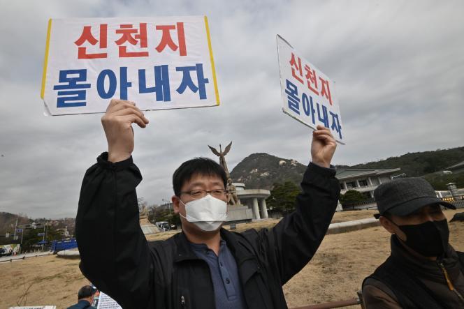 Le père d'une adepte de l'église Shincheonji de Jésus tient des pancartes«Chassons Shincheonji» lors d'un rassemblement à Séoul, le 12 mars.