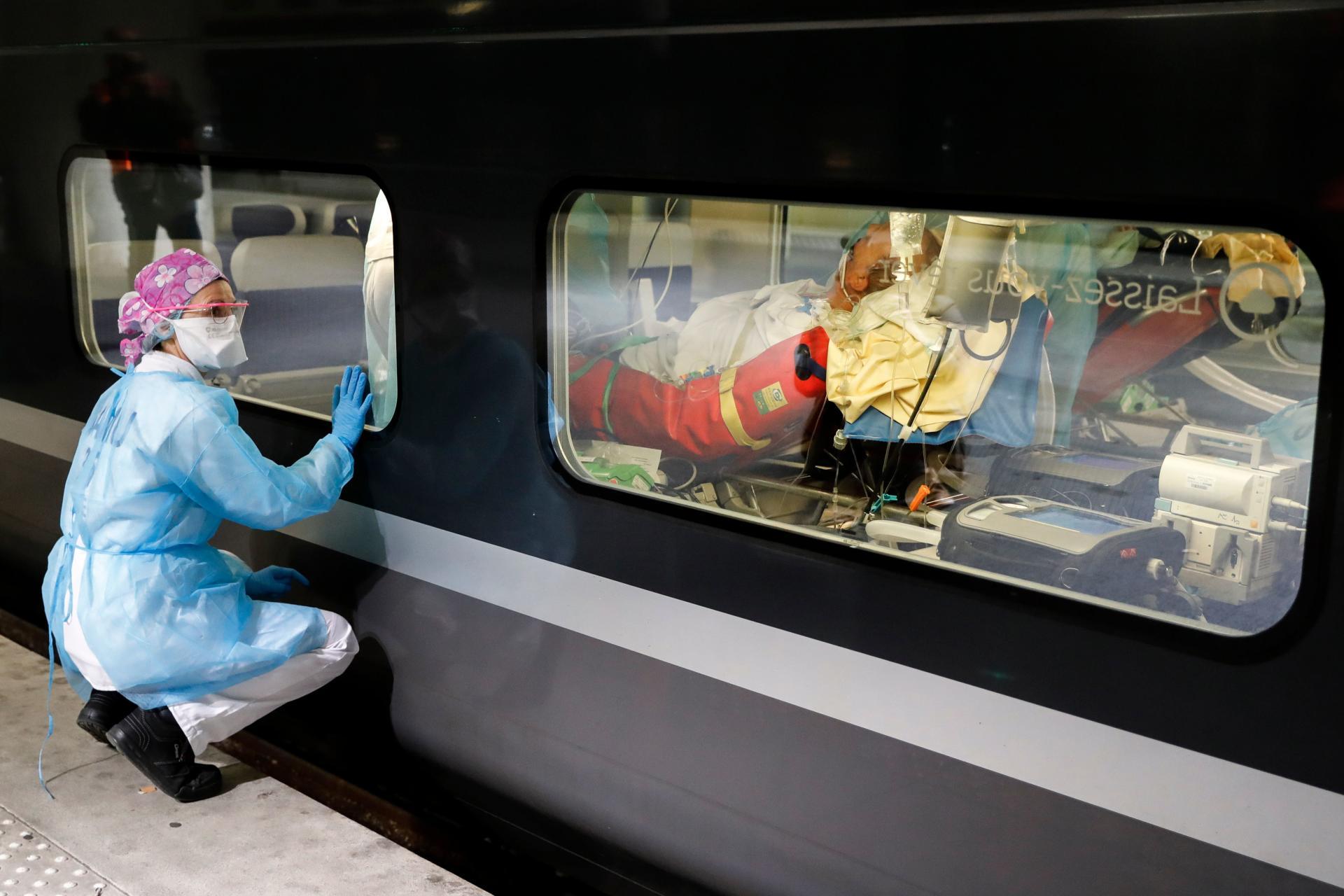 Une soignante observe un patient à travers la fenêtre du TGV.