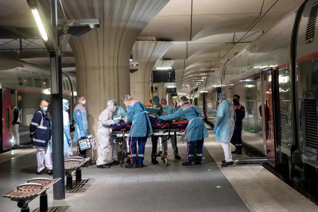 Des soignants transfèrent un patient à bord d'un TGV pour la Bretagne.