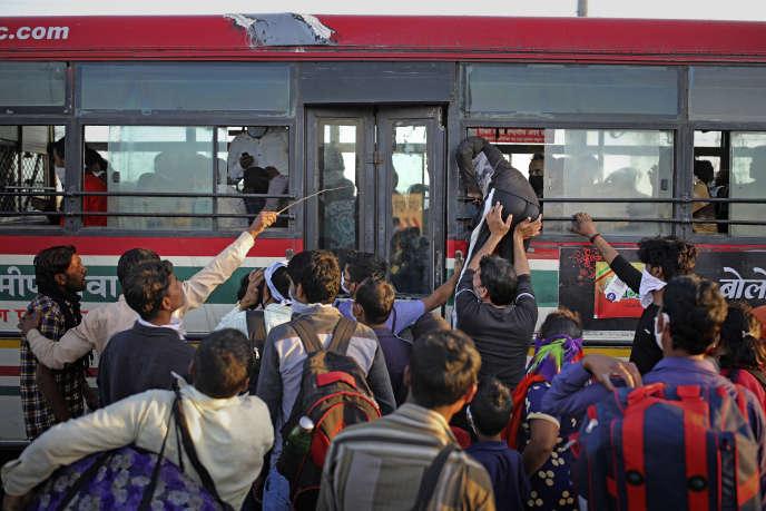 Des travailleurs tentent de monter dans un bus, le 28 mars, à New Delhi, pour rejoindre leur village après le confinement décidé par le gouvernement Modi, le 24 mars.