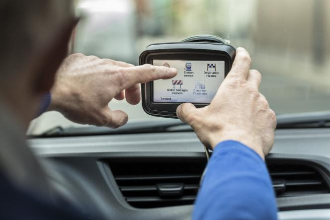 Le conducteur d'un véhicule hybride utilisant un GPS, à Paris.