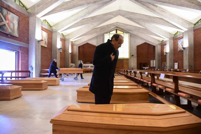 Don Mario, le curé de Seriate, au milieu des cercueils entreposés dans l'église San Giuseppe, le 26 mars à Seriate (Lombardie).