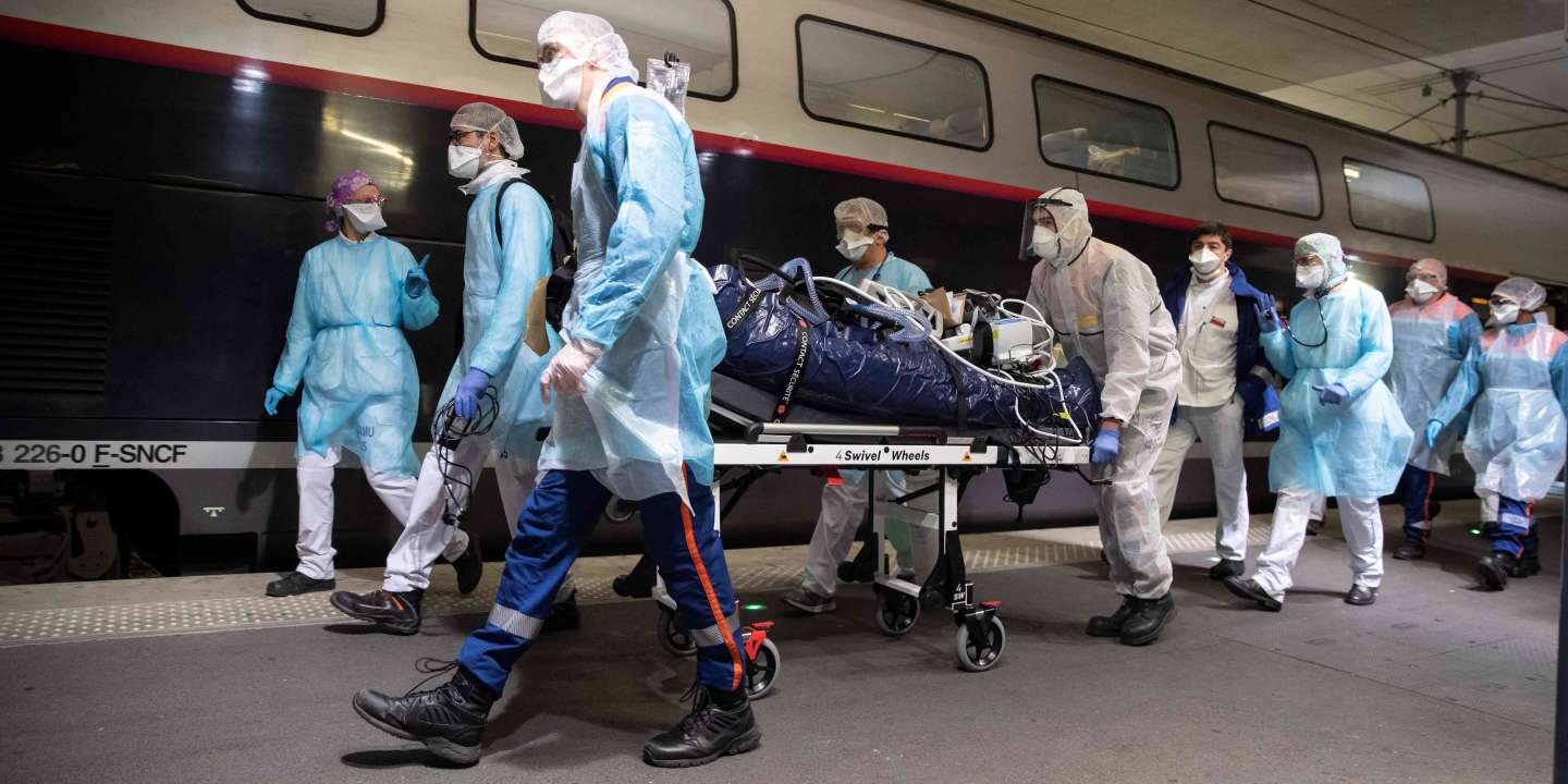 Medical staff carry a patient infected with the COVID-19 into a TGV high speed train at the Gare d'Austerlitz train station on April 1, 2020 in Paris, prior to his evacuation, along with 35 other patients in two separate medical TGV towards hospitals of Brittany, western France, where the outbreak of the Covid-19 pandemic caused by the novel coronavirus where  has been limited so far.  / AFP / POOL / Thomas SAMSON