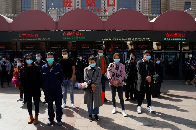 Des Pékinois observent trois minutes de recueillement en hommage aux victimes ducoronavirus, le 4 avril.
