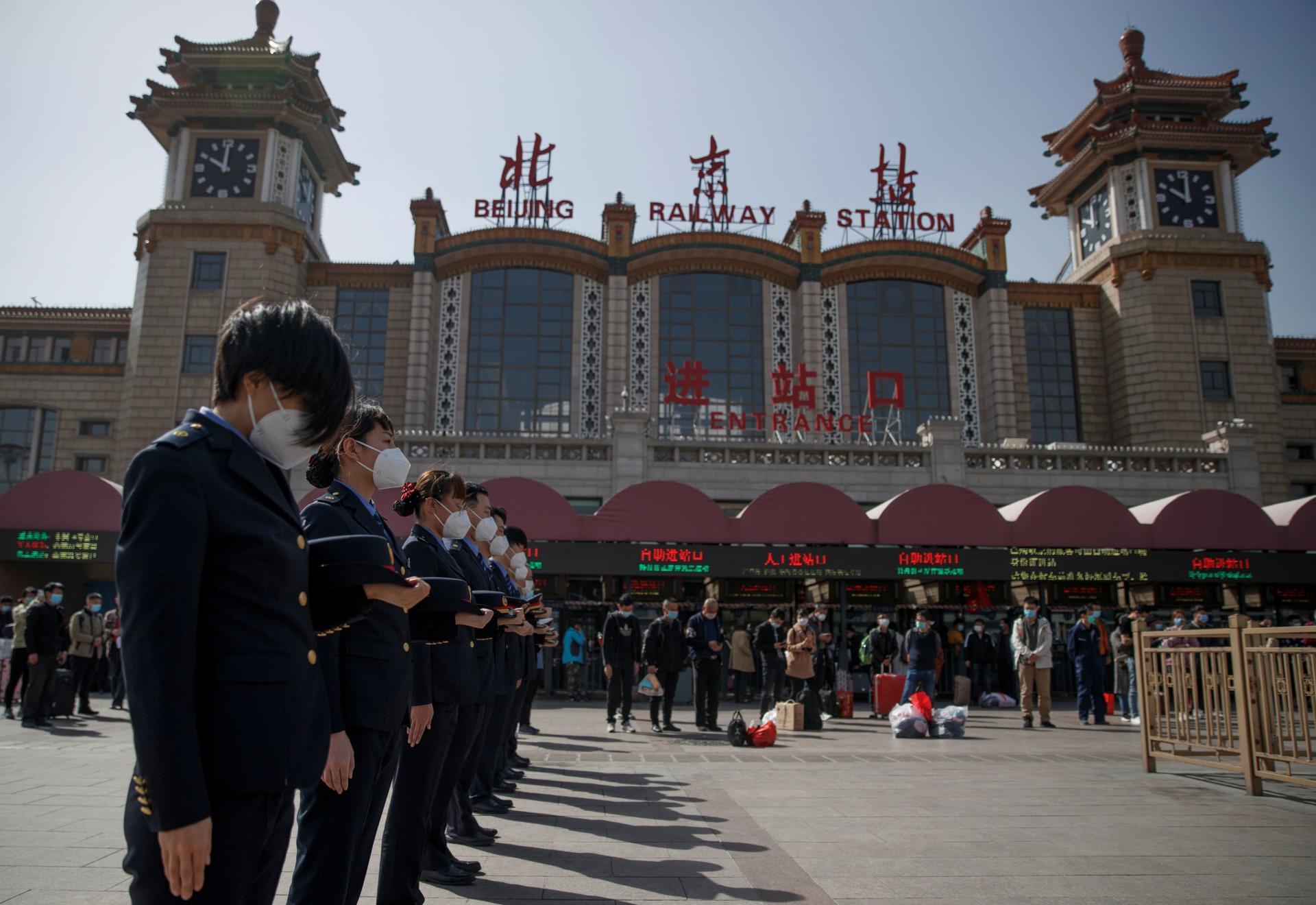 Les employés des chemins de fer rendent hommage aux morts du Covid-19, à la gare de Pékin, le 4 avril.