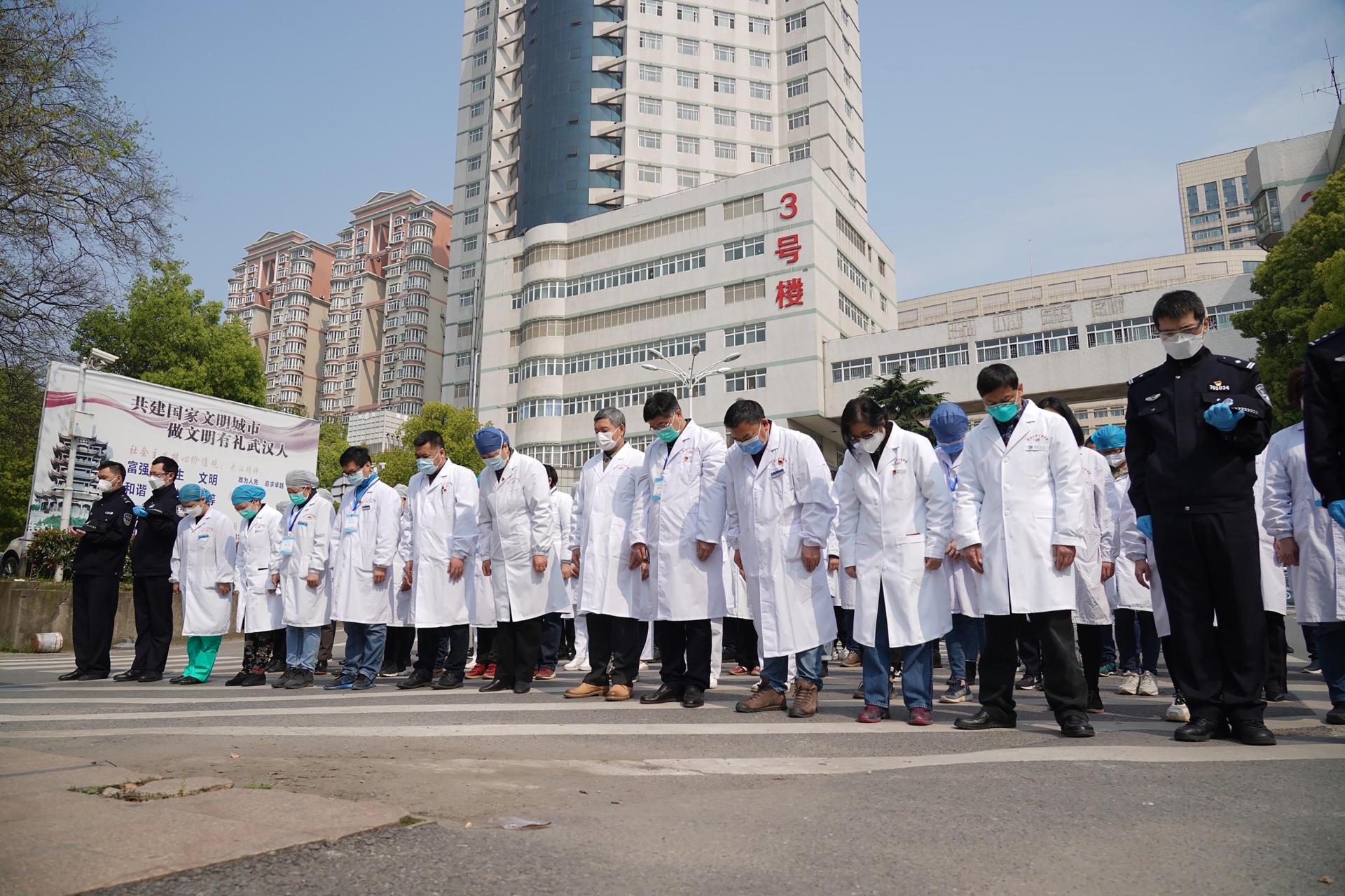 A Wuhan, des membres du personnel soignant de l'hôpital Tongji, en première ligne contre le Covid-19, se tenaient tête baissée devant le bâtiment principal.