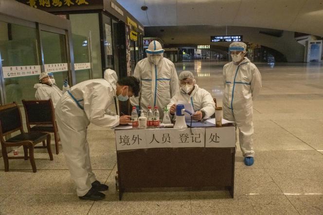 Une équipe du service d'enregistrement des passagers arrivant en gare de Wuhan. Leur température est prise, l'historique de leurs voyages récents analysés via une application téléphonique, ils sont ensuite dirigés vers le service d'acueil de leur district.Wuhan (Hubei), le 3 avril