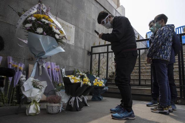 Des habitants masqués viennent se recueillir et déposer des fleurs en hommage aux morts de l'épidémie, à Wuhan.