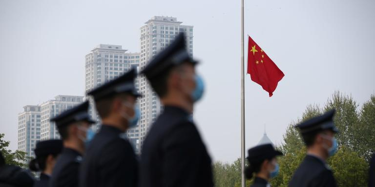 The Chinese national flag flies at half mast at a ceremony mourning those who died of the coronavirus disease (COVID-19) as China holds a nationwide mourning on the Qingming tomb-sweeping festival, in Wuhan, Hubei province, China April 4, 2020. China Daily via REUTERS  ATTENTION EDITORS - THIS IMAGE WAS PROVIDED BY A THIRD PARTY. CHINA OUT.