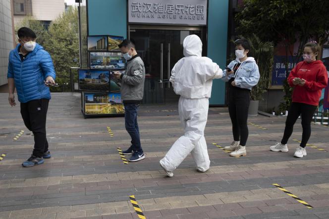 Devant un supermarché, un employé contrôle desattestations numériques d'absence de symptômes du Covid-19, à Wuhan (Chine), le 2 avril.