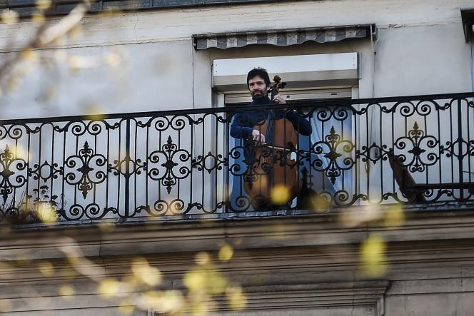 Le violoncelliste Camilo Peralta joue sur son balcon, à Paris, le 24 mars.