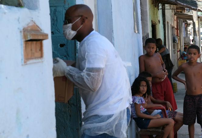 Un bénévole distribue des produits de première nécessité à des familles du bidonville Vila Kennedy à Rio de Janeiro, le 2 avril.