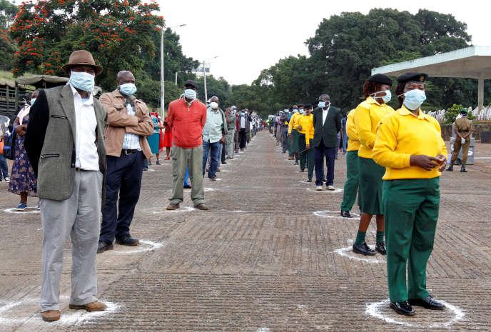 Les salariés du gouvernement du comté de Nairobi font la queue tout en observant la distanciation sociale pour collecter des lettres de redéploiement par les services métropolitains de la ville, le 6 avril 2020.