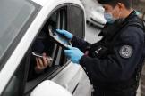 Un agent de police vérifie une attestation de sortie sur smartphone, à Paris, le 6 avril.