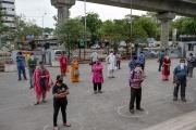 Des clients attendent de pouvoir entrer dans un supermarché, chacun dans un cercle marqué au sol, à Ahmedabad, en Inde, le 26 mars.
