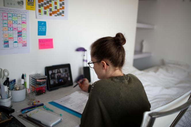 Une étudiante suit des cours à distance depuis sa chambre à Paris, le 20 mars.