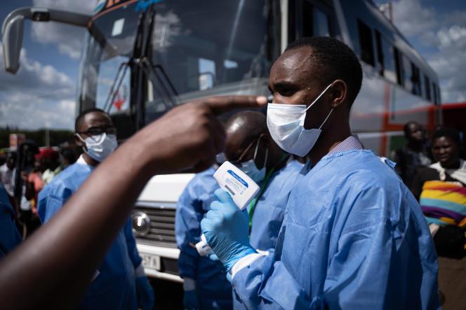 Un agent de santé contrôle les passagers d'un bus à Kigali, le 22mars 2020.