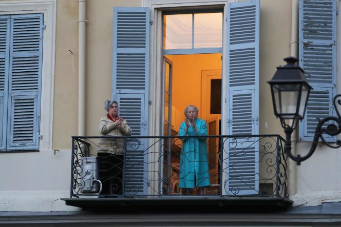 Des femmes applaudissent à leur balcon en soutien aux soignants à Nice, le 7 avril.
