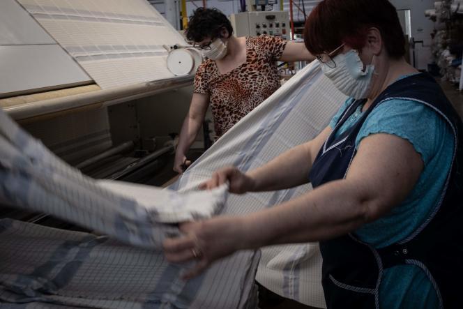 Des employées des Tissages de Charlieu confectionnent des masques de protection en tissu dans leur usine de la Loire, le 19 mars.
