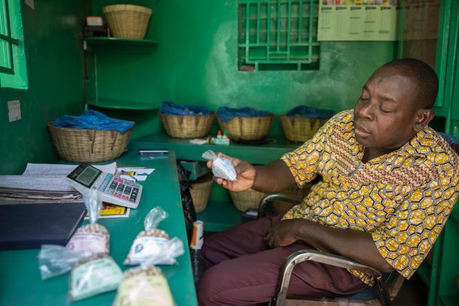 Un pharmacien, travaillant avec Jean-Baptiste Niéki, tient les gélules confectionnées par ce dernier, à Bamako.