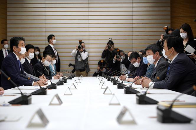 Le premier ministre japonais Shinzo Abe (à gauche) lors d'une réunion spéciale consacrée aux mesures prises pour contrer l'épidémie de coronavirus, le 6 avril.