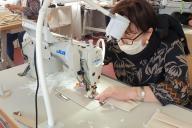 Dans les ateliers du groupe Boldoduc, une couturière confectionne des masques de protection.