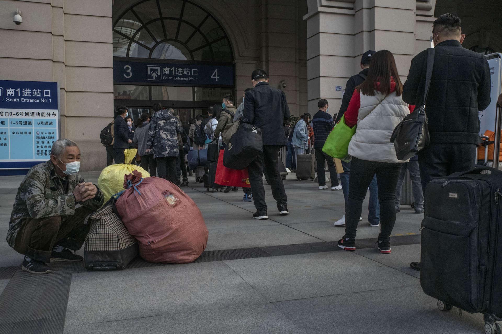 Un voyageur attend avec ses bagages pendant que d'autres rentrent dans la gare, le 8 avril à Wuhan.