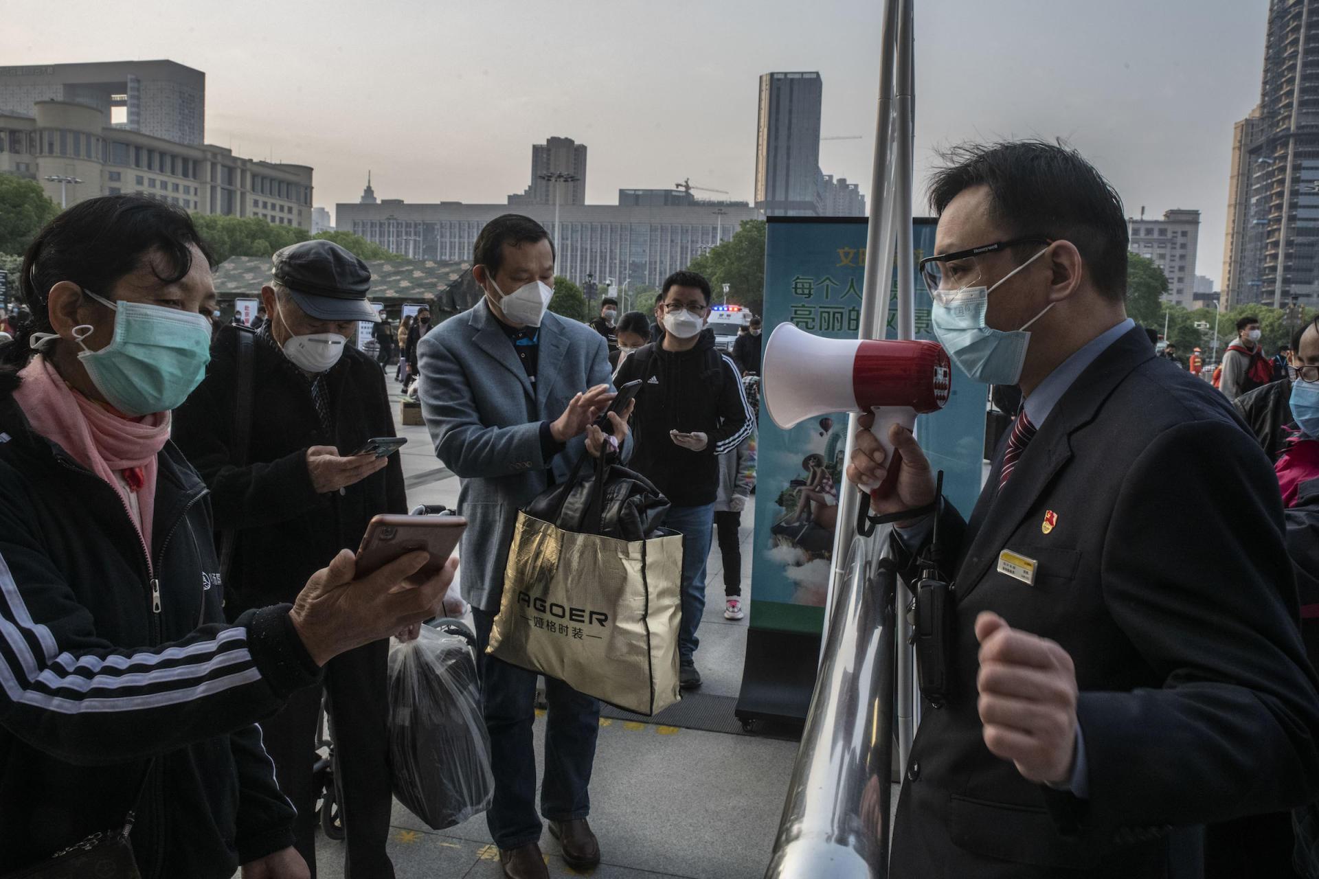 Le jour de l'autorisation des départs depuis Wuhan, un employé de la gare de Hankou aide les passagers à scanner le code QR conditionnant leur voyage, le 8 avril à Wuhan, dans la province de Hubei.