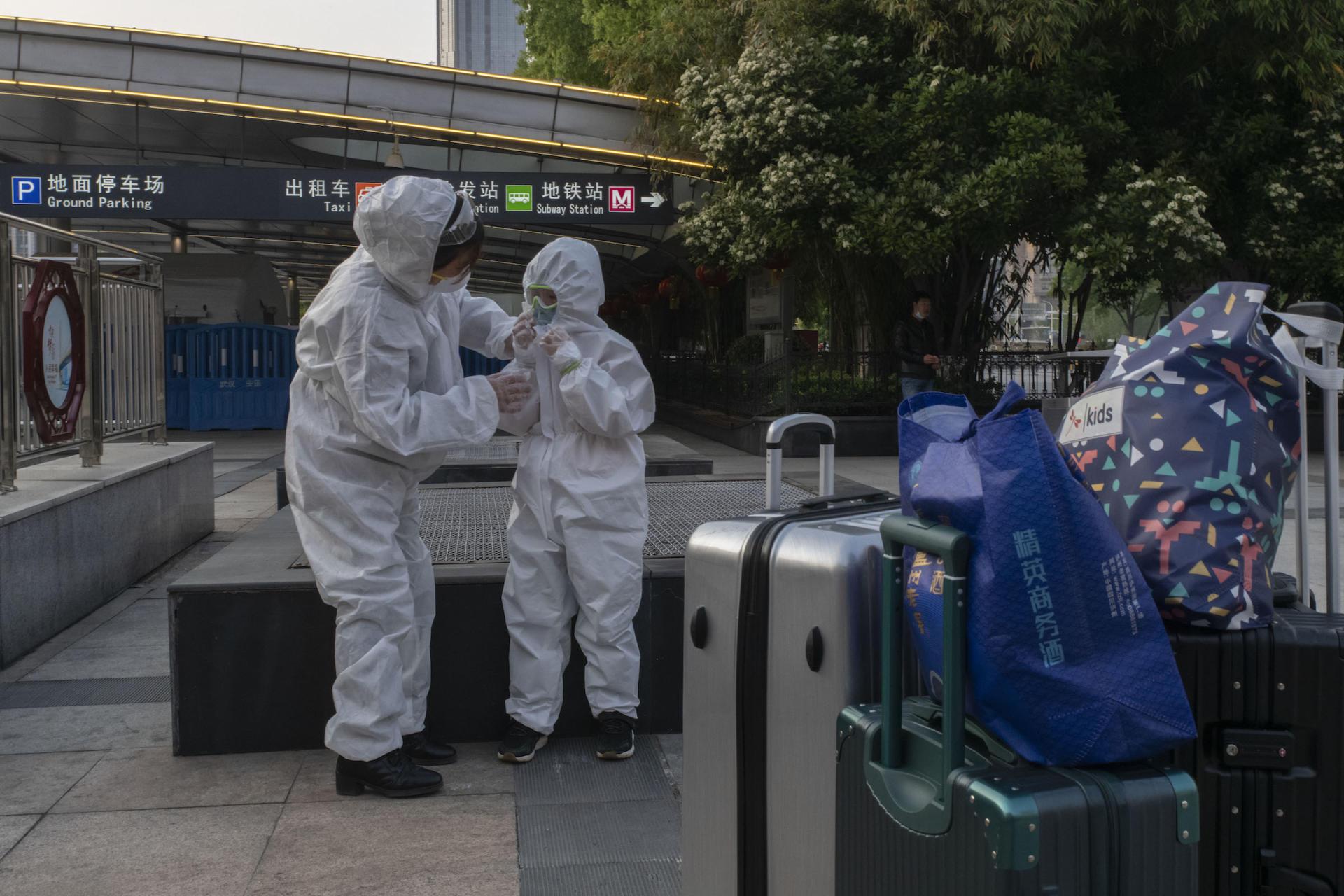 En gare de Hankou, le 8 avril à Wuhan, Bai Cuixiang aide son petit-fils (7 ans) à réajuster son masque avant leur départ pour Shanghaï après avoir passé plus de deux mois en confinement.