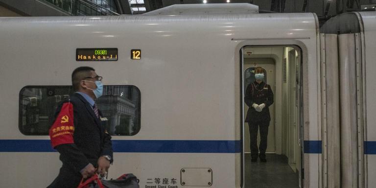 Wuhan (Hubei), le 8 avril 2020 En gare de Hankou, un enmployé porte les bagages d'un passager embarquant dans l'un des premiers trains officiels au départ de la ville depuis la levée du confinement à minuit. Le 8 avril est le jour officiel de la réouverture de Wuhan. Même si beaucoup d'habitants restent encore confinés, beaucoup des contraintes de déplacements sont levés avec des niveaux variables en fonction des quartiers et du statut des résidents (santé, occupation professionnelle). Gilles Sabrié pour Le Monde