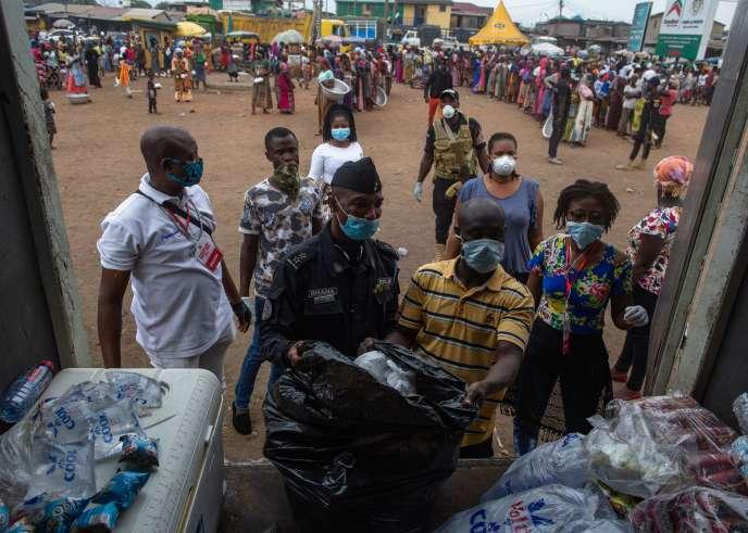 Un policier participe à la distribution de nourriture pour la population en confinement à Accra, au Ghana, le 4 avril.