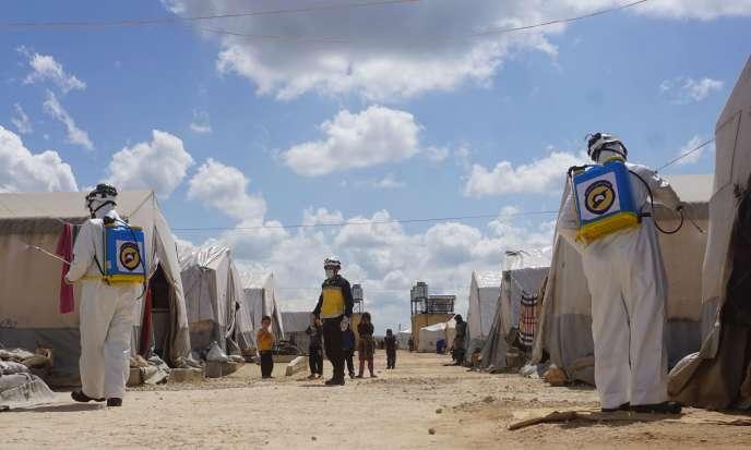 La défense civile syrienne vaporise du désinfectant sur les tentes d'un camp de déplacés près de la ville de Maaret Misrin, dans la province d'Idlib, le 9 avril 2020.