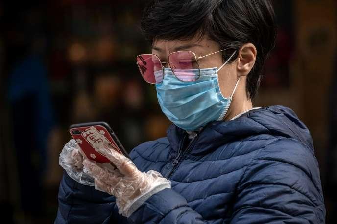 Une femme, masquée et gantée, consulte son smartphone, à Pékin, le 9 avril.