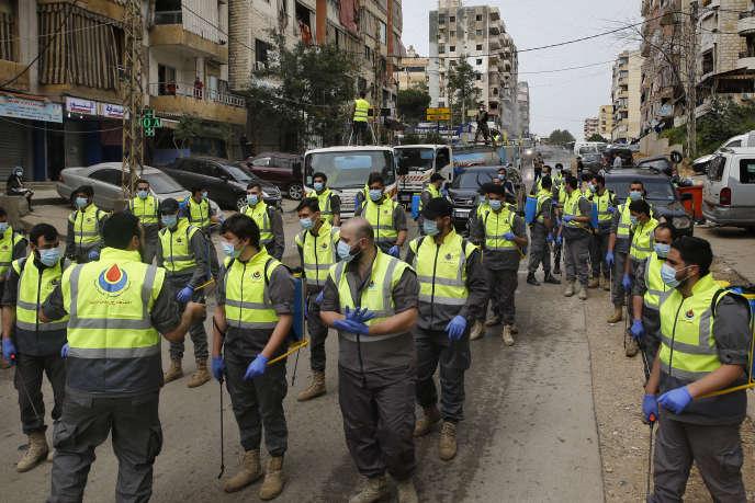 Des membres de la Société islamique de la santé, une branche du mouvement pro-iranien Hezbollah, se préparent à pulvériser du désinfectant contre l'épidémiedue au coronavirus, dans une banlieue sud de Beyrouth, au Liban, le 27 mars.