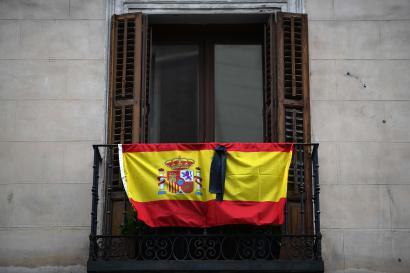 Un drapeau espagnol avec un ruban noir pour rendre hommage aux victimes du coronavirus, est accroché sur un balcon à Madrid le 9 avril 2020.