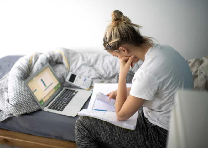 Nina, 17 ans, en classe de Terminale ES, travaille dans sa chambre pendant le confinement dû au covid-19. Elle lit un message de sa professeur principale envoyé avant les vacances scolaires.