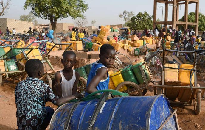 Des enfants patientent pour une distribution d'eau, à Taabtenga, quartier de Ouagadougou, la capitale du Burkina Faso, le 3 avril 2020.