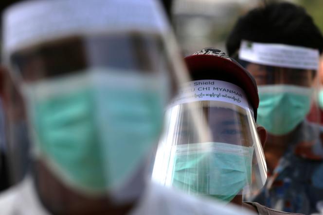 Des assistants de moines bouddhistes protégés par des boucliers faciaux collectent les aumônes à Rangoun, en Birmanie, le 10 avril 2020.