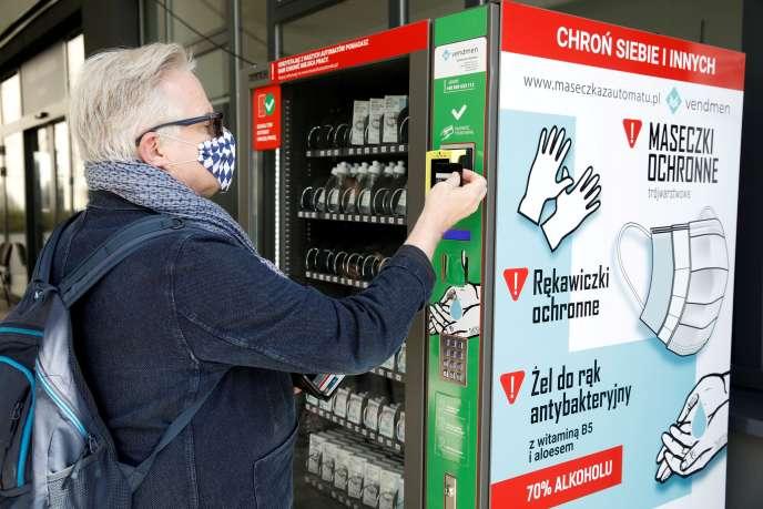 Un homme achète des gants dans un distributeur, dans une rue de Varsovie, le 10avril.